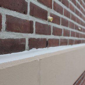 Afkitten van de boven en onderzijden van de betonbanden aansluiting metselwerk.