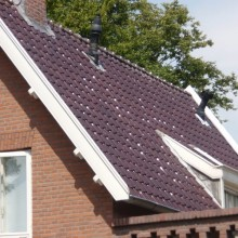 Het pannendak na de dakrenovatie met nieuwe dakpannen.